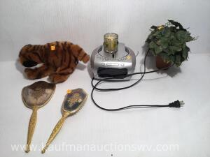 Alarm clock/radio/CD player, dresser mirror and brush, stuffed tiger, floral arrangement